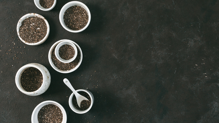 Organic chia seeds on black tabletop. Set of small bowls with organic chia seed. Superfood concept. Copy space. Top view or flat-lay. Banner
