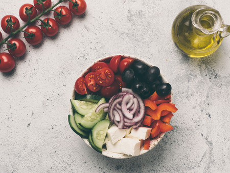 Greek Salad Bowl on gray cement background, copy space. Above view of Bowl Greek Salad. Trendy food. Idea, recept and concept of modern healthy food. Toned image.