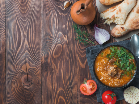 Traditional Georgian kitchen Kharcho soup with meat,rice,fresh cilantro.Spicy soup Kharcho on wooden table with traditional bread Shotis Puri,vintage wine jar,vegetables. Copy space for text. Top view