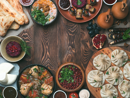 View from above of georgian cuisine on brown wooden table.Traditional georgian food-khinkali,kharcho,chahokhbili,phali,lobio and local sauces - tkemali, satsebeli, adzhika.Top view.Copy space for text Banco de Imagens