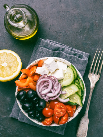 Greek Salad Bowl on dark black background. Above view of Bowl Greek Salad. Trendy food. Idea, recept and concept of modern healthy food. Vertical. Copy space for text. Stock fotó