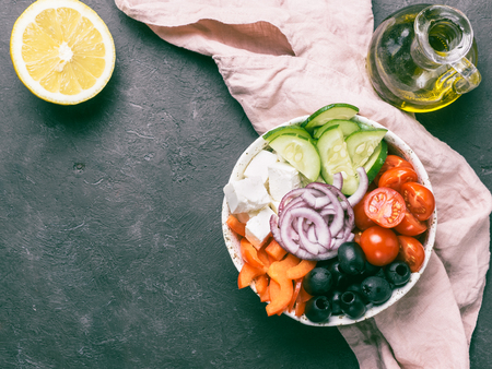 Greek Salad Bowl on dark black background, copy space. Above view of Bowl Greek Salad. Trendy food. Idea, recept and concept of modern healthy food.