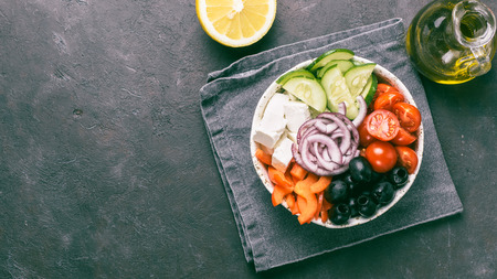 Greek Salad Bowl on dark black background, copy space. Above view of Bowl Greek Salad and ingredients. Trendy food. Idea, recept and concept of modern healthy food. Banner. Toned image. Stock fotó