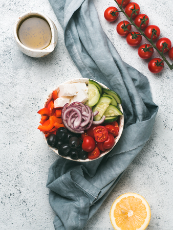 Greek Salad Bowl on gray cement background, copy space. Above view of Bowl Greek Salad. Trendy food. Idea, recept and concept of modern healthy food. Vertical.