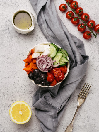 Greek Salad Bowl on gray cement background, copy space. Above view of Bowl Greek Salad. Trendy food. Idea, recept and concept of modern healthy food. Vertical. Toned image.