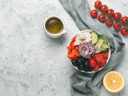 Greek Salad Bowl on gray cement background, copy space. Above view of Bowl Greek Salad. Trendy food. Idea, recept and concept of modern healthy food.