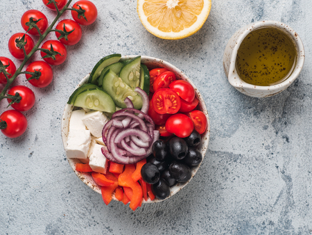 Greek Salad Bowl on gray cement background. Above view of Bowl Greek Salad with olive oil and ingredients. Trendy food. Idea, recept and concept of modern healthy food. Copy space for text.