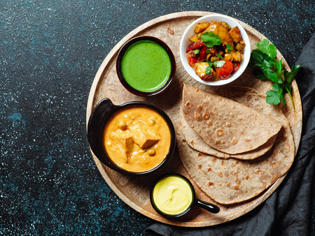 Indian cuisine dishes: vegetable curry, shahi paneer, chapati, chutney. Indian food on wooden tray over dark background. Assortment indian meal with copy space for text. Top view or flat lay.