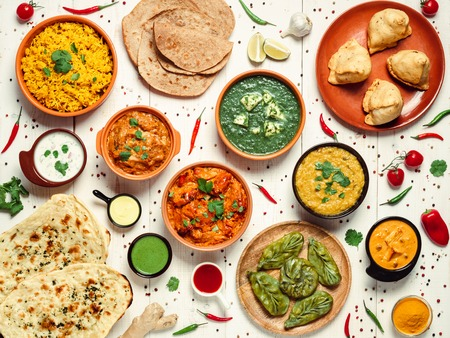 Indian cuisine dishes: tikka masala, dal, paneer, samosa, chapati, chutney, spices. Indian food on white wooden background. Assortment indian meal top view or flat lay. Stock Photo