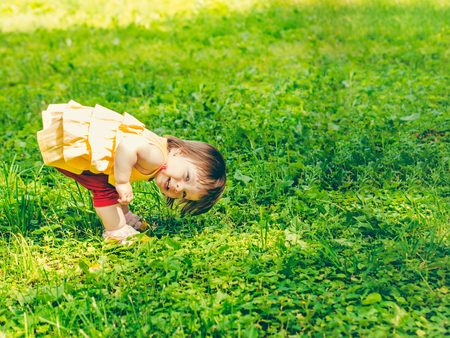 One-year baby girl playing upside down on street Stockfoto
