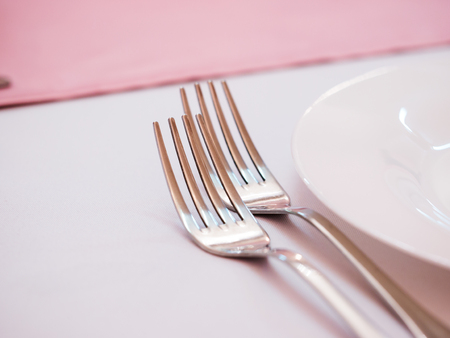 Two kitchen forks on dinner table with pink tablecloth