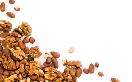 Background of mixed nuts - hazelnuts, walnuts, almonds - with copy space. Nuts isolated one edge. Assortment nuts top view or flat lay Imagens