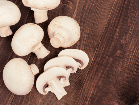 Fresh white champignon mushrooms close up on dark brown wooden background with copyspace. Flat lay or top view