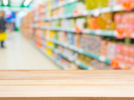 Blurred colorful supermarket products on shelves and perspective table for mockup
