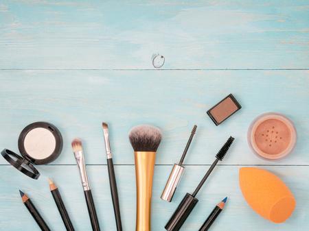 Set of make up on turquoise wooden background. Mascara brush, eyebrow gel brush, pencil, eyeshadow, sponge and brushes. Mock up with copyspace. Shallow DOF Stock fotó