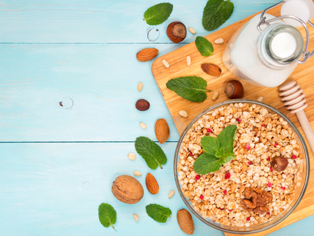 Colorful health breakfast concept. Muesli, milk and nuts on blue wooden background. Top view or flat lay. Copy space Stock fotó