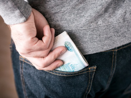 his hand put russian rubles in jeans pocket or take out from pocket
