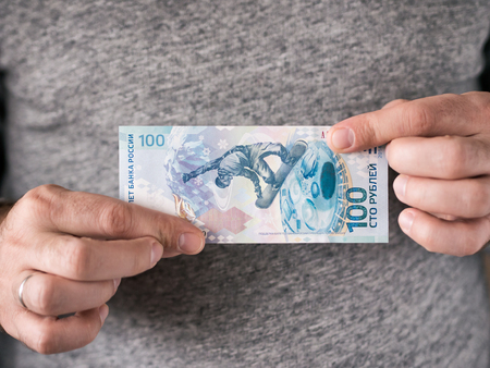 Hands hold russian rubles. Anniversary banknote of one hundred russian rubles in mens hands.. Selective focus. Shallow DOF Stock Photo