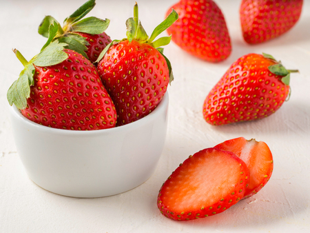 Fresh ripe strawberries in small white bowl. Strawberry in bowl on oriental white background