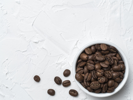 Coffee beans with copy space. Brown coffee beans on white concrete textured background. Top view or flat lay. Copy space.