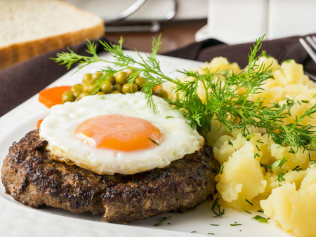 Beefsteak with fried egg and mashed potatoes on white plate close-up on dark brown wooden table in restaurant