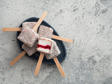 Homemade raw lamington ice cream pops on gray background. Australian sweet dessert lamington with chia and raspberries jam, chocolate and cocoa coat. Vegan food recipe and idea. Copy space. Top view