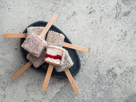Homemade raw lamington ice cream pops on gray background. Australian sweet dessert lamington with chia and raspberries jam, chocolate and cocoa coat. Vegan food recipe and idea. Copy space. Top view Reklamní fotografie - 123144097