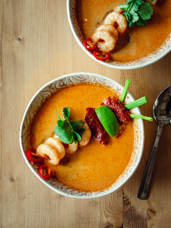 Tom yam kong ready-to-eat. Tom yum soup with shrimps on wooden table. Popular spicy Thai dish Tom Yam top view. Thailand food and Thai cuisine. Vertical. Natural day light