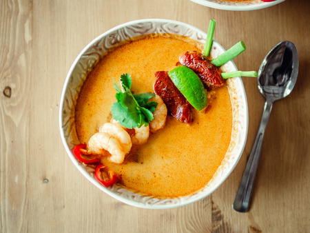 Tom yam kong ready-to-eat. Tom yum soup with shrimps on wooden table. Popular spicy Thai dish Tom Yam top view. Thailand food and Thai cuisine. Natural day light