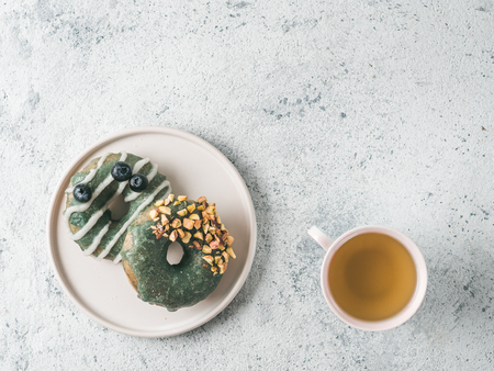 Vegan doughnuts with chia seeds topped with healthy spirulina glaze with pistachio and blueberry. Blue green spirulina donuts and herbal tea cup on gray background, top view or flat lay. Copy space