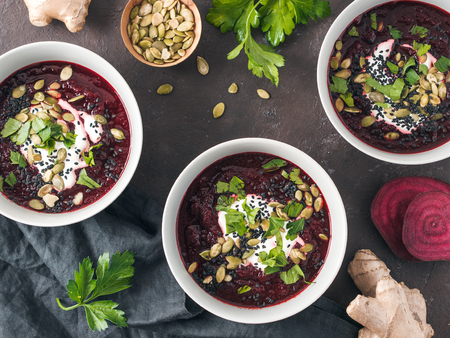 Ideas and recipes for healthy soup - Beetroot and ginger soup puree. Clean eating, detox, vegetarian diet concept. Top view of plate with perfect beet soup, dressed pepitas, sesame and parsley