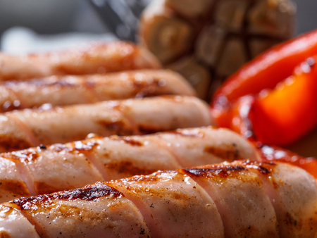 Close up view of chicken homemade sausages. Grilled sausages and grilled vegetables. Copy space.