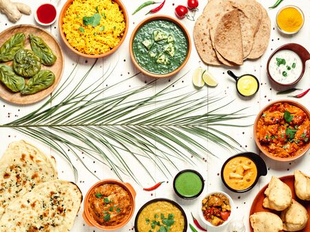 Indian cuisine dishes: tikka masala, dal, paneer, samosa, chapati, chutney, spices. Indian food on white wooden background. Assortment indian meal with copy space for text. Top view or flat lay.