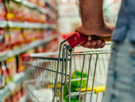 shopping trolley in supermarket aisle, copy space
