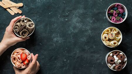 Hands with rolled ice cream in cone cups on dark background. Different iced rolls top view or flat lay. Thai style rolled ice cream with copy space in center for text or design. Banner Stock Photo