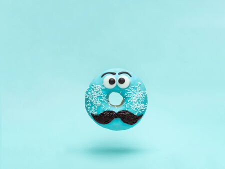 Blue glazed donut with mustache. Flying blue doughnut with funny face with mustache over blue background. Copy space for text. Masculinity or father day concept. 版權商用圖片