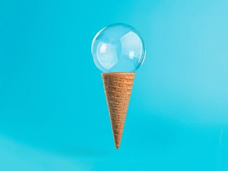 Ice cream cone with soap bubble on blue background Imagens