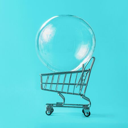 Shopping cart with soap bubble on blue background