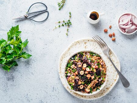 Warm buckwheat and beetroot salad on gray background. Vegetarian diet idea and recipe -salad with beetroot, buckwheat, mushrooms, onion, fresh herbs,hazelnut. Top view or flat-lay. Copy space for text