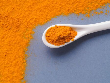 Turmeric Powder or Curcuma longa and white spoon with turmeric powder on gray background. Top view. Copy space for text. Фото со стока