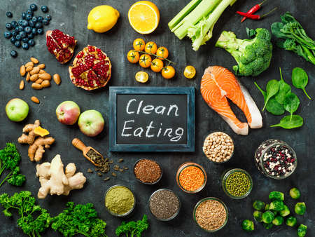 Clean Eating concept. Selection food ingredients and chalkboard with Clean Eating words on dark background. Top view or flat lay. Stock Photo