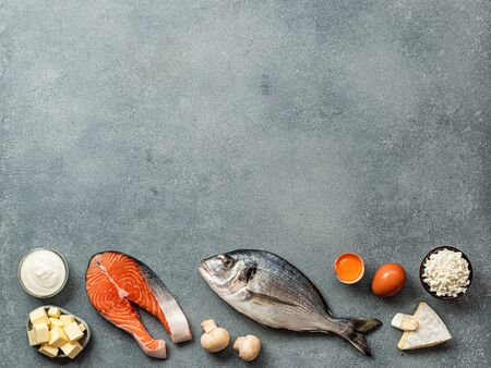 Vaitamin D sources concept with copy space for text. Fish, salmon, dairy products, eggs, mushrooms on gray stone background. Top view or flat lay. Copy space top