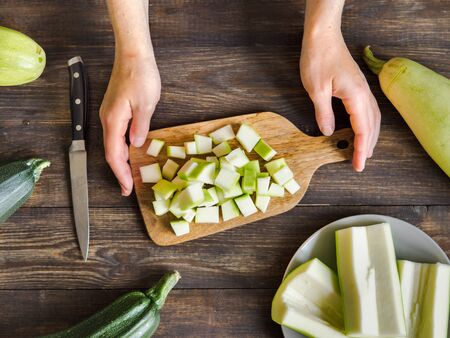 Zucchini harvest. Woman slices zucchini cubes for freezing on wooden table. Farm organic zucchini harvesting Top view or flat lay.