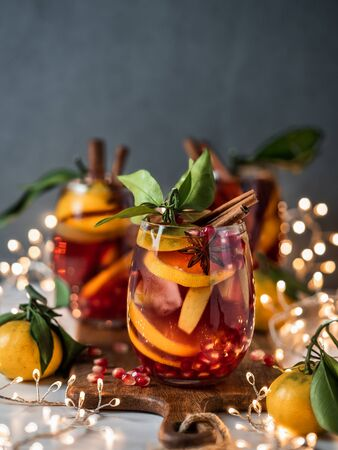 Winter sangria on dark christmas holiday background. Jugful of sangria and glasses with fruit slice, pomegranate and spices. Copy space for text or design. Vertical. 스톡 콘텐츠 - 132714528