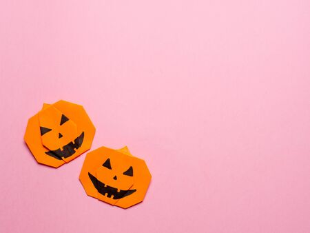 Halloween concept. Paper origami pumpkin on pink background. Simple idea for halloween - easy made paper pumpkins on trendy color Ceylon Yellow background. Copy space for text. Stock Photo