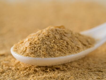 Nutritional yeast background. Nutritional inactive yeast in white spoon. Copy space. Nutritional yeast is vegetarian superfood with cheese flavor, for healthy diet