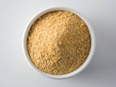 Nutritional yeast background. Nutritional inactive yeast in small white ctramic bowl. Copy space. Top view. Nutritional yeast is vegetarian superfood with cheese flavor, for healthy diet