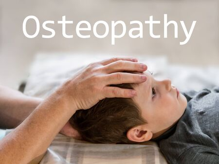 Osteopathy Treatment and word Osteopathy. Elementary age boys forehead being manipulated by real osteopathic physician