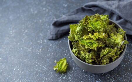 Green Kale Chips with salt in bowl. Homemade healthy snack for low carb, keto, low calorie diet. Dark blue background. Ready-to-eat kale chips, copy space left. Banner
