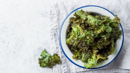 Green Kale Chips with salt on plate. Homemade healthy snack for low carb, keto, low calorie diet. Gray cement background. Ready-to-eat kale chips, copy space for text. Top view or flat lay. Banner